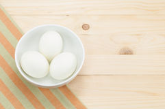 Fresh duck egg in bowl on napery and wood background. Stock Image
