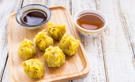 Fresh dumplings with hot steams and tea on wood plate. Chinese food on wooden background Stock Photos