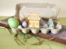 Fresh and Easter painted chicken and quail eggs in a packing tray, a toy house with illumination on a green table with scattered. Hay, the concept of cozy stock photography