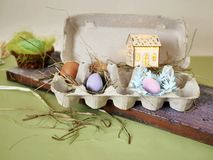 Fresh and Easter painted chicken and quail eggs in a packing tray, a toy house with illumination on a green table with scattered. Hay, the concept of cozy royalty free stock photography