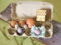 Fresh and Easter painted chicken and quail eggs in a packing tray, a toy house with illumination on a green table with scattered. Hay, the concept of cozy royalty free stock photos