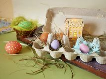 Fresh and Easter painted chicken and quail eggs in a packing tray, a toy house with illumination on a green table with scattered. Hay, the concept of cozy stock photos