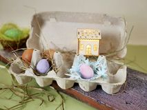 Fresh and Easter painted chicken and quail eggs in a packing tray, a toy house with illumination on a green table with scattered. Hay, the concept of cozy stock image