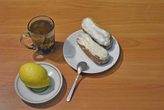 Fresh eclair with white chocolate a cup of tea and lemon.jpg. Fresh eclair with white chocolate, a cup of tea and lemon, top view Royalty Free Stock Photography