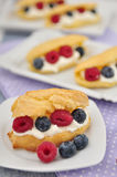 Fresh eclairs with whipped cream and berries Royalty Free Stock Image