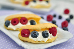 Fresh eclairs with whipped cream and berries Stock Photos