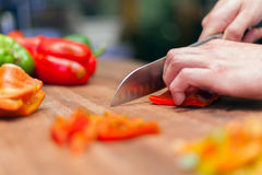 Fresh ecological Bell pepper chopped on cutting board hands Royalty Free Stock Photo