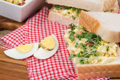 Fresh egg and bacn on white sandwich in rustic kitchen setting Stock Image