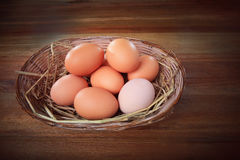 Fresh egg in bamboo basket on wood table Stock Photos