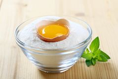 Fresh egg in a bowl of flour Stock Image
