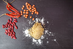 Fresh egg in flour , Peanuts with red lentils and noodles and wooden rolling on black chalkboard. Royalty Free Stock Photography