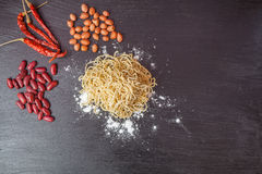 Fresh egg in flour , Peanuts with red lentils and noodles and wooden rolling on black chalkboard. Stock Image