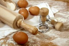Eggs, flour, ravioli stamp and rolling pin on a wooden table royalty free stock image