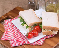 Fresh egg and rocket on white sandwich in rustic kitchen setting Stock Photo