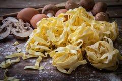Italian fresh pasta. Fresh egg tagliatelle italian homemade pasta on wooden board Royalty Free Stock Images