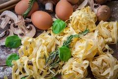 Italian fresh pasta. Fresh egg tagliatelle italian homemade pasta on wooden board Stock Image