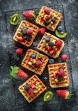 Fresh egg waffles dessert for breakfast with fruits strawberries, blueberries, blackberries, raspberries and kiwi.  stock images
