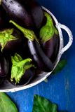 Fresh eggplant in grey basket on blue wooden table.Rustic background. Top view. Copy space. Vegan vegetable. Stock Image