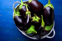 Fresh eggplant in grey basket on blue wooden table.Rustic background. Top view. Copy space. Vegan vegetable. Stock Photo
