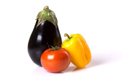 Fresh eggplant, tomato, paprika isolated on the white background. Fresh colourful vegetables: purple eggplant, red tomato, yellow paprika isolated on the white Stock Images