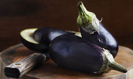 Fresh eggplant on wooden cutting board with knife. Deliciously Royalty Free Stock Photography