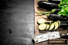 Fresh eggplants with an old knife and slices. On the black chalkboard Stock Photos