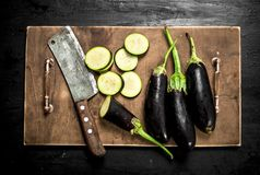 Fresh eggplants with an old knife and slices. On the black chalkboard Stock Photography