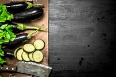 Fresh eggplants with an old knife and slices. On the black chalkboard Royalty Free Stock Images
