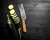 Fresh eggplants with an old knife and slices. On the black chalkboard Royalty Free Stock Photo