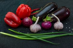 Fresh eggplants, pepper, garlic, onion on black background royalty free stock photo