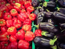 Fresh eggplants and sweet peppers at the market. Closeup of eggplants and sweet peppers on display at the market Stock Photos