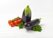 Fresh eggplants, tomatoes and sage. Two fresh eggplants, tomatoes and sage on white wooden background Stock Image