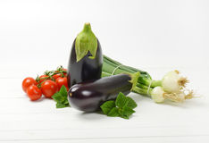 Fresh eggplants, tomatoes and spring onion. On white wooden background Stock Image