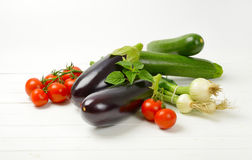 Fresh eggplants, tomatoes, zucchini and spring onion. On white wooden background Stock Photography
