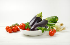 Fresh eggplants, tomatoes, zucchini and spring onion. On white wooden background Royalty Free Stock Images