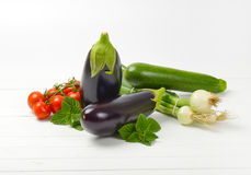 Fresh eggplants, tomatoes, zucchini and spring onion. On white wooden background Royalty Free Stock Photo