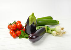 Fresh eggplants, tomatoes, zucchini and spring onion. On white wooden background Royalty Free Stock Photography