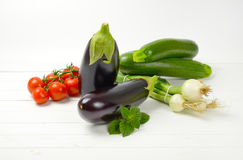 Fresh eggplants, tomatoes, zucchini and spring onion. On white wooden background Stock Photos