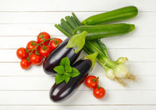 Fresh eggplants, tomatoes, zucchini and spring onion. On white wooden background Stock Image