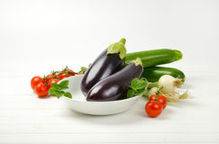 Fresh eggplants, tomatoes, zucchini and spring onion. On white wooden background Stock Photo