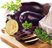 Fresh eggplants. On a wooden border on white . Selective focus royalty free stock photo