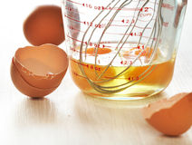 Fresh eggs. In a glass bowl and metal whisk with a raw egg in a measuring cup Stock Photos