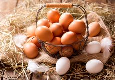 Fresh eggs in a basket. On wooden table Royalty Free Stock Photography