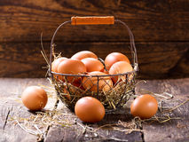 Fresh eggs in a basket. On wooden table Stock Photography