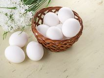 Fresh eggs in a basket and on a wooden table. Against the background of white flowers. Basket with fresh eggs on a wooden table with flowers. Natural healthy Royalty Free Stock Photography