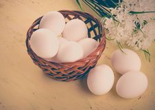 Fresh eggs in a basket and on a wooden table. Basket with fresh eggs on a wooden table with flowers Stock Image