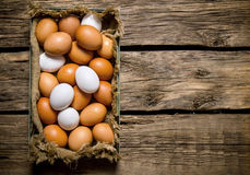 Fresh eggs from the box. On wooden table. Fresh eggs from the box. On a wooden table.  Free space for text . Top view Stock Photo