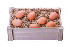 Fresh Eggs. Bunch of Fresh Brown Eggs and Some Straw in a Wooden Crate Isolated on a White Background royalty free stock photo