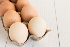 Fresh eggs in carton package on white wood background. Horizontal photo Stock Images