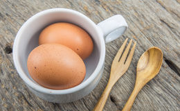 Fresh eggs with cup and spoon Royalty Free Stock Photography